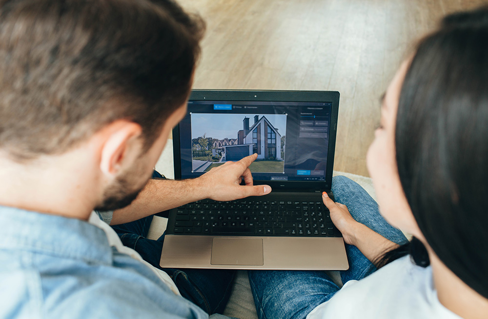 Couple pointing at real estate on laptop screen.