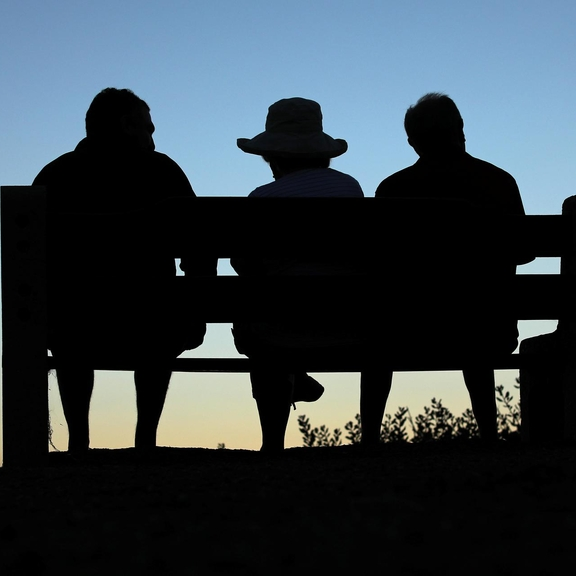 Three olders adults sitting on a bench at sunset.