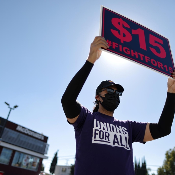 "Masked person holding ""Fight for $15"" sign."