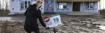 "Woman planting ""sold"" sign in front of house under construction."