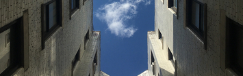View of the sky looking up through the courtyard of an apartment building.